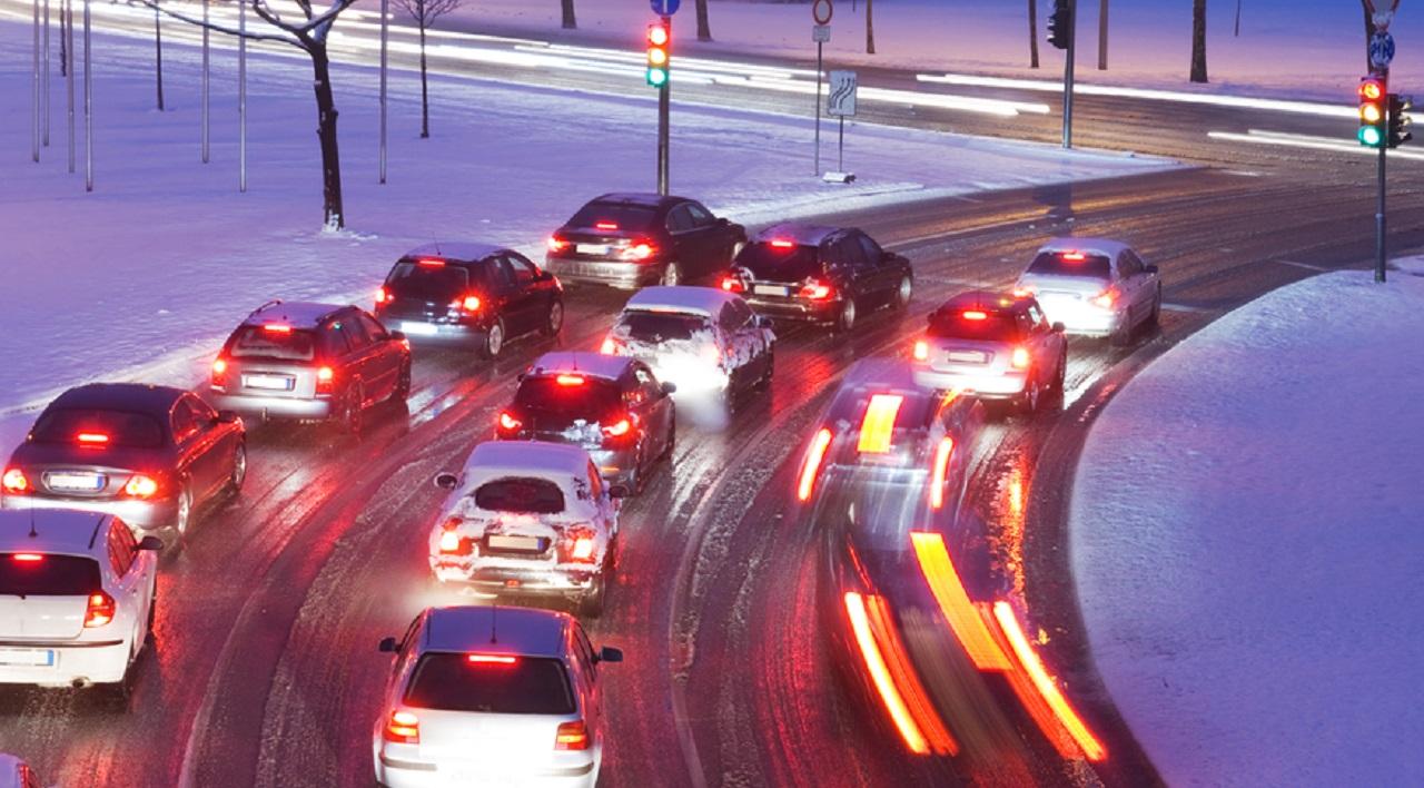 biler-holder-taet-ved-lyskryds-på-vej-med-sjap-og-sne