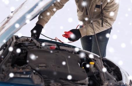 mand-der-sætter-startkabler-på-bil-i-snevejr