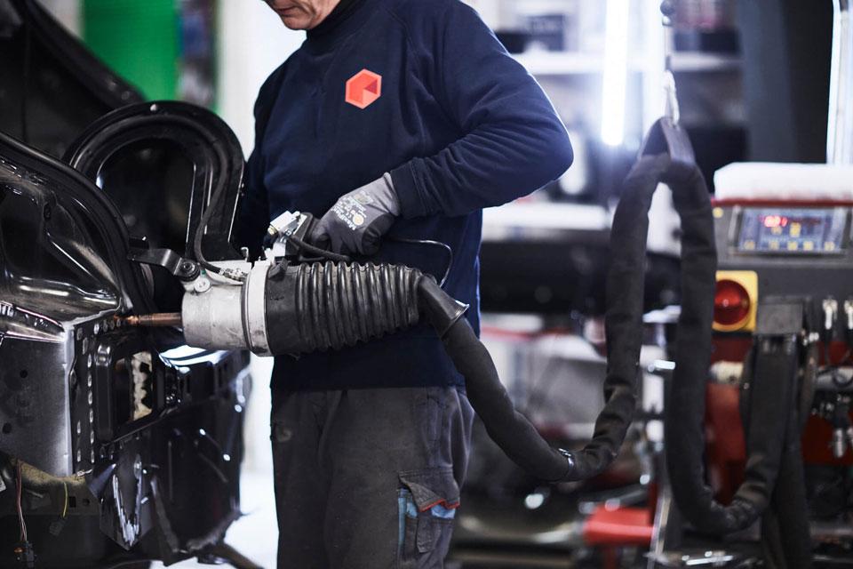 SKG-Mekaniker-udbedrer-skade-på-bil-med-oprette-vaerktøj